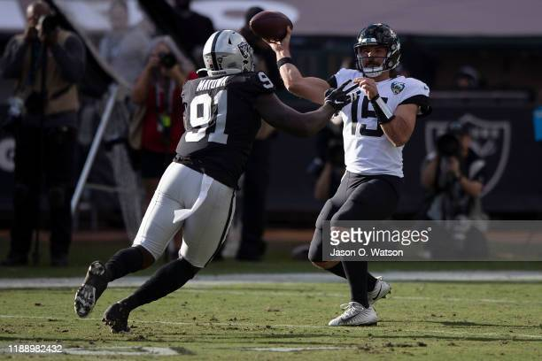 Quarterback Gardner Minshew II of the Jacksonville Jaguars is pressured by defensive end Benson Mayowa of the Oakland Raiders during the second...