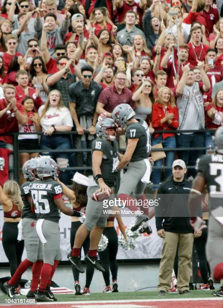 Quarterback Gardner Minshew II of the Washington State Cougars celebrates with teammate Kyle Sweet after a touchdown in the first half against the...