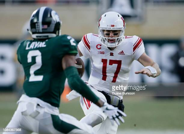 Quarterback Giovanni Rescigno of the Rutgers Scarlet Knights scrambles against cornerback Justin Layne of the Michigan State Spartans during the...