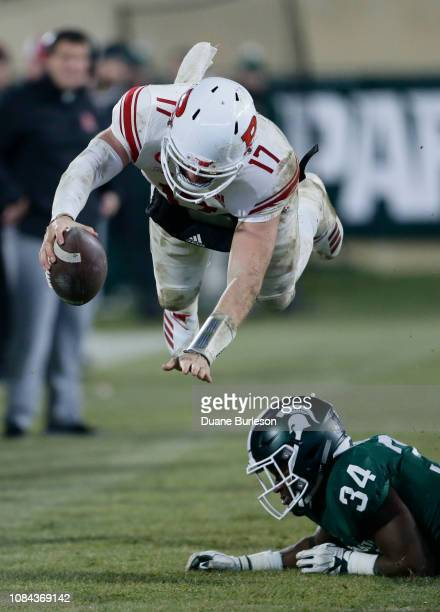 Quarterback Giovanni Rescigno of the Rutgers Scarlet Knights dives over linebacker Antjuan Simmons of the Michigan State Spartans while carrying the...