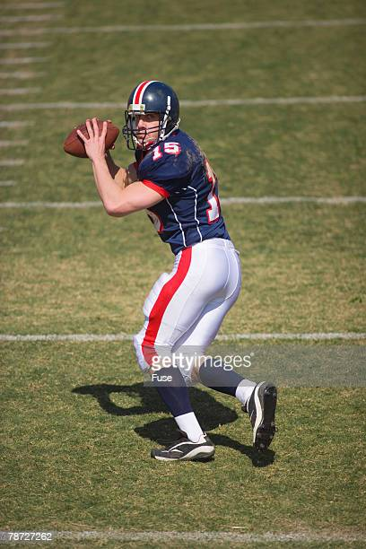 quarterback going back to pass - quarterback photos et images de collection