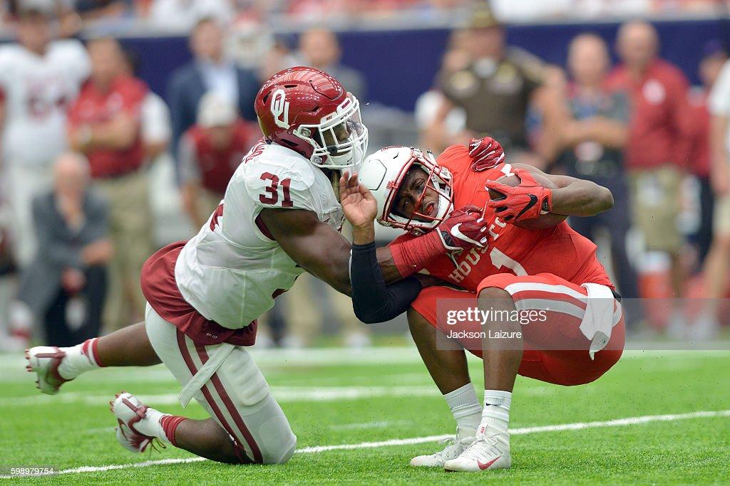 Quarterback Greg Ward Jr. #1 of the Houston Cougars is tackled by linebacker Ogbonnia Okoronkwo #31of the Oklahoma Sooners on Saturday September 3, 2016 at NRG Stadium in Houston, Texas.