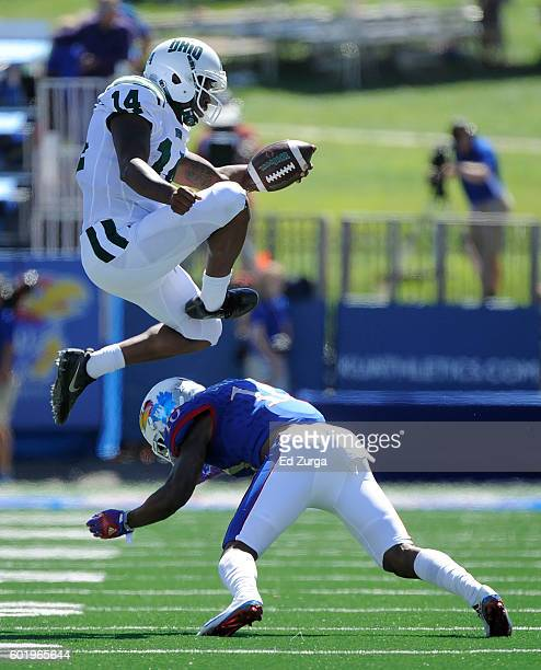 Quarterback Greg Windham of the Ohio Bobcats leaps over cornerback Marnez Ogletree of the Kansas Jayhawks as he picks up a first down in the first...