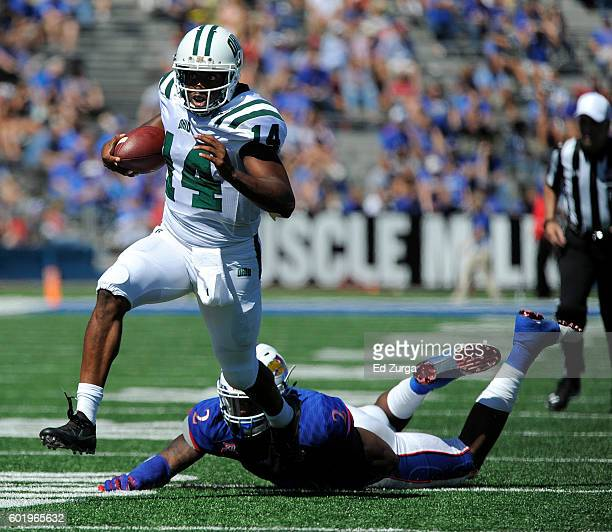 Quarterback Greg Windham of the Ohio Bobcats slips past Dorance Armstrong Jr #2 of the Kansas Jayhawks as he runs for a touchdown in the second...