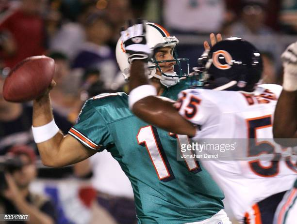 Quarterback Gus Frerotte of the Miami Dolphins tries to throw under pressure from linebacker Lance Briggs of the Chicago Bears during the NFL Hall of...