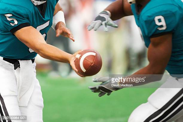 quarterback handing off football to running back, mid section - passing sport stockfoto's en -beelden