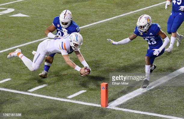 Quarterback Hank Bachmeier of the Boise State Broncos dives to score on a 2-yard touchdown run against defensive lineman Jay Kakiva and cornerback...