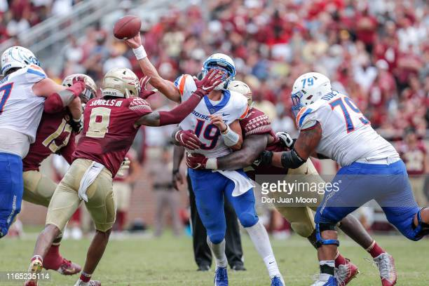 Quarterback Hank Bachmeier of the Boise State Broncos is sacked by Defensive Tackle Marvin Wilson and Cornerback Stanford Samuels III of the Florida...