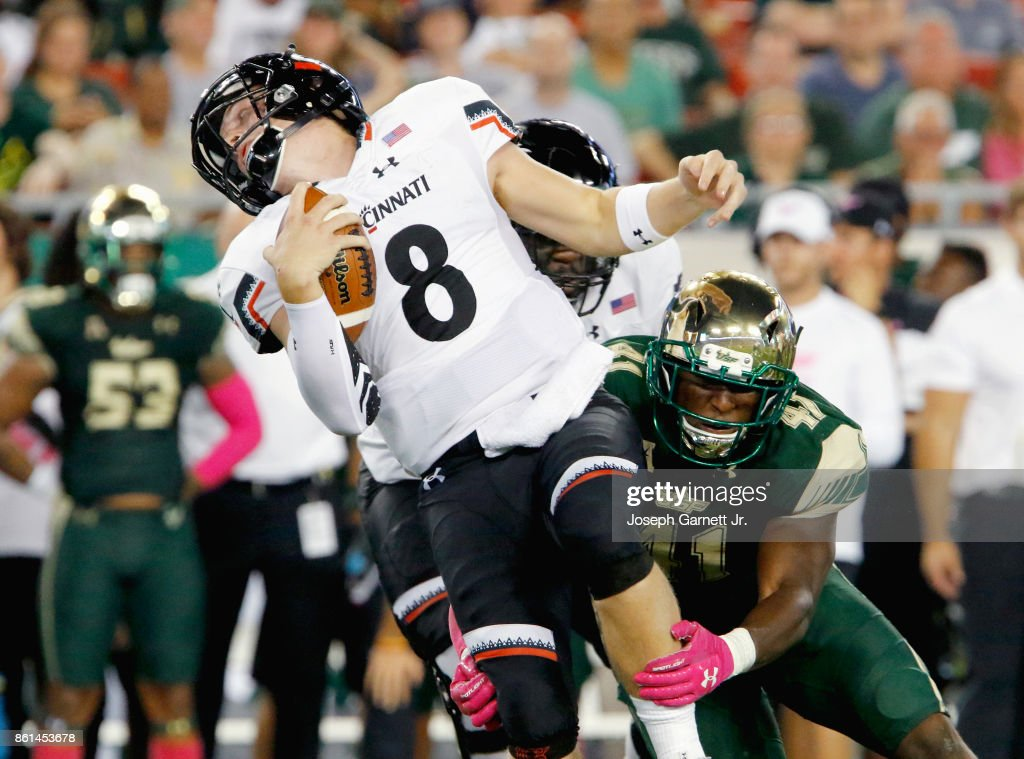 Quarterback Hayden Moore #8 of the Cincinnati Bearcats is tackled by defensive end Greg Reaves #41 of the South Florida Bulls during the second quarter of their game at Raymond James Stadium on October 14, 2017 in Tampa, Florida.