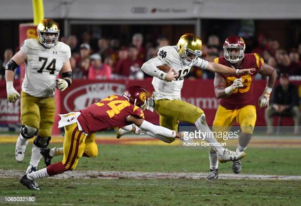 Quarterback Ian Book of the Notre Dame Fighting Irish eludes a tackle by Isaiah Langley of the USC Trojans during the second half at Los Angeles...