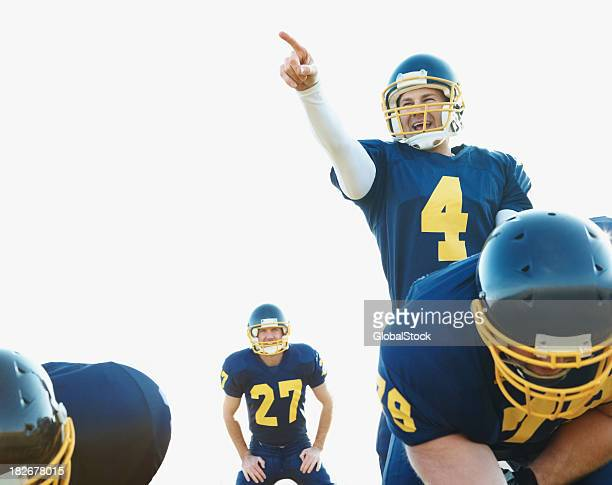 quarterback in action directing the next tackle - quarterback stock photos and pictures