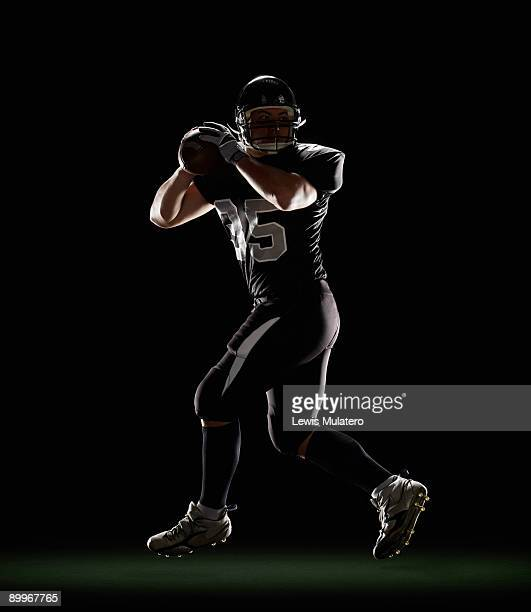 quarterback in three-step drop position - quarterback stock-fotos und bilder