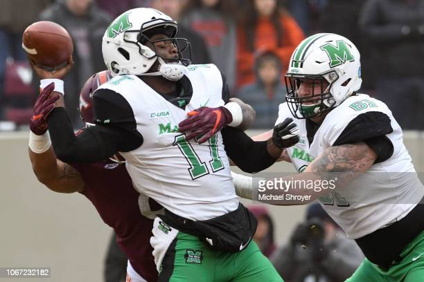 Quarterback Isaiah Green of the Marshall Thundering Herd fumbles after being hit by defensive lineman Ricky Walker of the Virginia Tech Hokies in the...