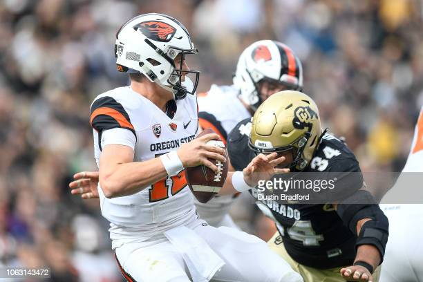 Quarterback Jack Colletto of the Oregon State Beavers attempts to throw a pass under pressure by defensive lineman Mustafa Johnson of the Colorado...