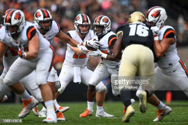 Quarterback Jack Colletto of the Oregon State Beavers hands off to running back Jermar Jefferson in the second quarter of a game against the Colorado...