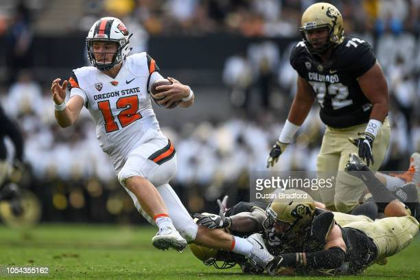 Quarterback Jack Colletto of the Oregon State Beavers is sacked by Colorado Buffaloes including defensive end Chris Mulumba at Folsom Field on...