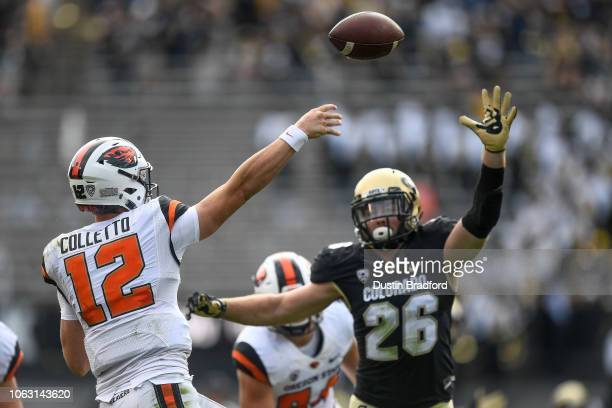 Quarterback Jack Colletto of the Oregon State Beavers passes under pressure by linebacker Carson Wells of the Colorado Buffaloes at Folsom Field on...