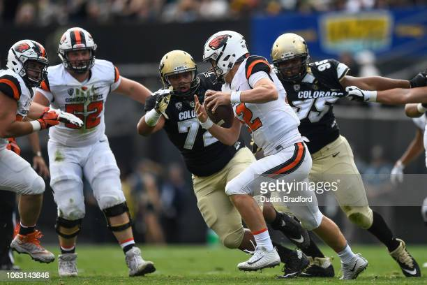 quarterback Jack Colletto of the Oregon State Beavers scrambles to evade a tackle attempt by nose tackle Lyle Tuiloma of the Colorado Buffaloes at...