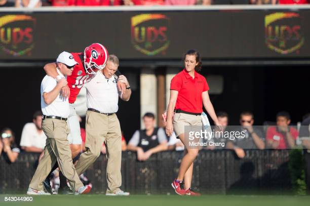 Quarterback Jacob Eason of the Georgia Bulldogs gets help from trainers after injuring his leg during their game against the Appalachian State...