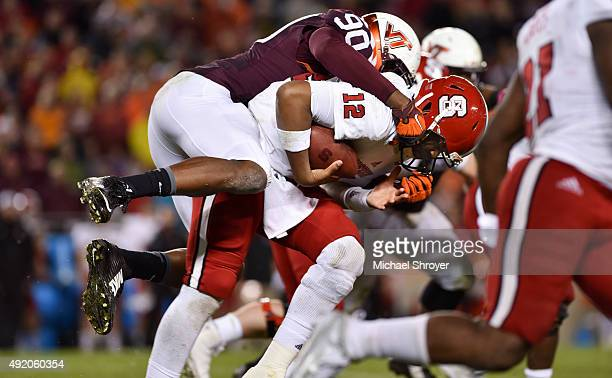 Quarterback Jacoby Brissett of the North Carolina State Wolfpack is sacked by defensive end Dadi Nicolas of the Virginia Tech Hokies in the first...
