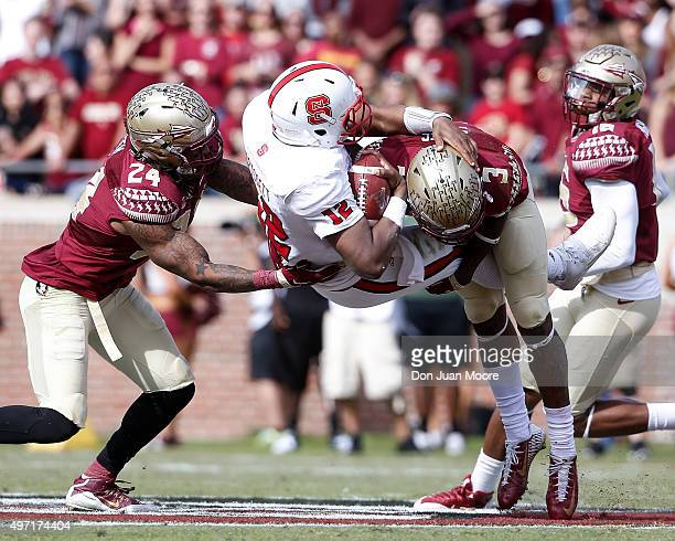 Quarterback Jacoby Brissett of the North Carolina State Wolfpack is sacked by Linebacker Terrance Smith and Cornerback Derwin James during the game...