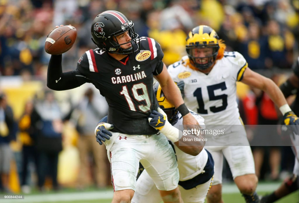 Quarterback Jake Bentley #19 of the South Carolina Gamecocks looks for a receiver while getting pressure from defensive lineman Maurice Hurst #73 of the Michigan Wolverines during the third quarter of the Outback Bowl NCAA college football game on January 1, 2018 at Raymond James Stadium in Tampa, Florida.
