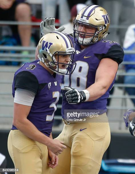 Quarterback Jake Browning of the Washington Huskies is congratulated by Kaleb McGary after scoring a touchdown against the Montana Grizzlies at Husky...
