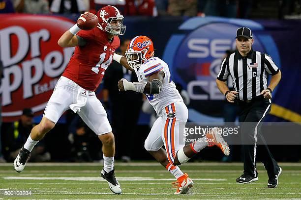 Quarterback Jake Coker of the Alabama Crimson Tide scrambles under pressure from linebacker Jarrad Davis of the Florida Gators in the first quarter...