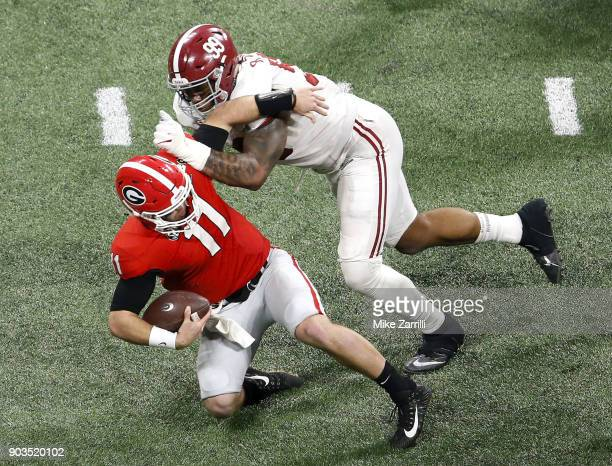 Quarterback Jake Fromm of the Georgia Bulldogs is tackled by defensive end Raekwon Davis of the Alabama Crimson Tide during the College Football...