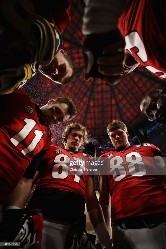 Quarterback Jake Fromm #11, tight end Miles McGinty #87 and linebacker Jaden Hunter #88 of the Georgia Bulldogs huddle together following the CFP National Championship presented by AT&T against the Alabama Crimson Tide at Mercedes-Benz Stadium on January 8, 2018 in Atlanta, Georgia. The Crimson Tide defeated the Bulldogs 26-23.