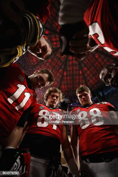 Quarterback Jake Fromm, tight end Miles McGinty and linebacker Jaden Hunter of the Georgia Bulldogs huddle together following the CFP National...
