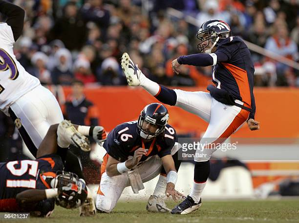 Quarterback Jake Plummer of the Denver Broncos holds the ball so kicker Jason Elam can attempt to score against the Baltimore Ravens during the game...