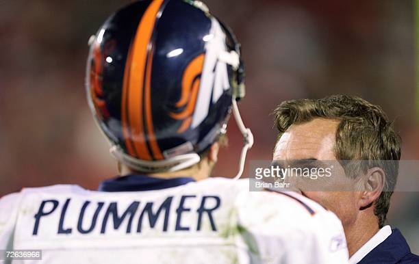 Quarterback Jake Plummer talks with head coach Mike Shanahan of the Denver Broncos after throwing an incomplete pass on fourth down in the final two...