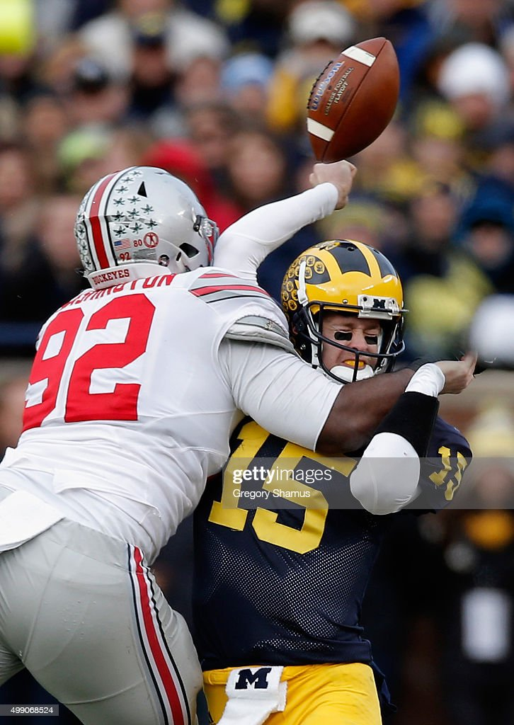 Quarterback Jake Rudock #15 of the Michigan Wolverines fumbles the ball while being hit by Adolphus Washington #92 of the Ohio State Buckeyes in the third quarter at Michigan Stadium on November 28, 2015 in Ann Arbor, Michigan.