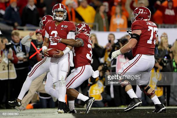Quarterback Jalen Hurts of the Alabama Crimson Tide celebrates with teammates after rushing for a 30yard touchdown during the fourth quarter against...