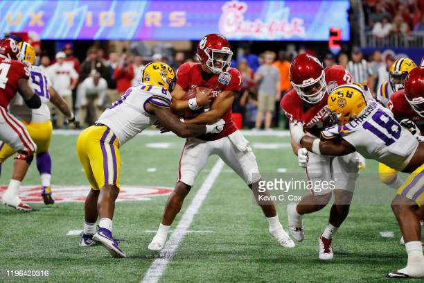 Quarterback Jalen Hurts of the Oklahoma Sooners is sacked by linebacker Patrick Queen of the LSU Tigers during the ChickfilA Peach Bowl at...