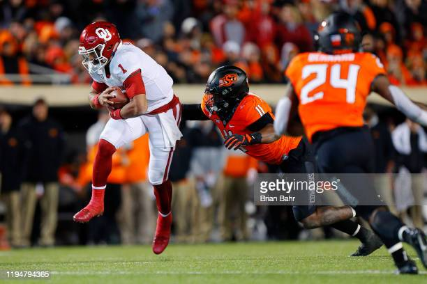 Quarterback Jalen Hurts of the Oklahoma Sooners switches direction against linebacker Amen Ogbongbemiga of the Oklahoma State Cowboys in the fourth...