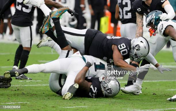 Quarterback Jalen Hurts of the Philadelphia Eagles is tackled by defensive tackles Quinton Jefferson and Johnathan Hankins of the Las Vegas Raiders...