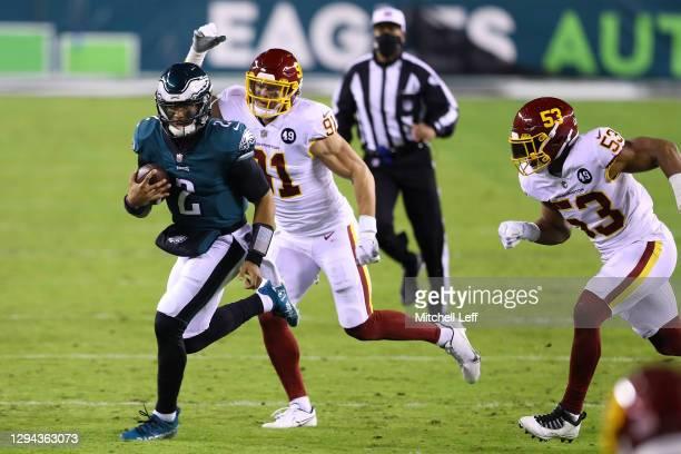 Quarterback Jalen Hurts of the Philadelphia Eagles scrambles against pressure from defensive end Ryan Kerrigan of the Washington Football Team during...