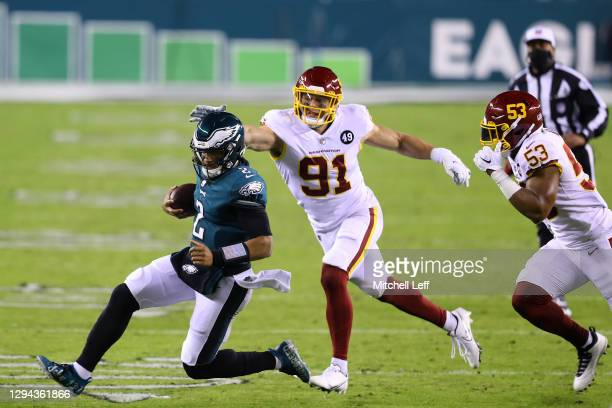 Quarterback Jalen Hurts of the Philadelphia Eagles slides as he is pursued by defensive end Ryan Kerrigan of the Washington Football Team during the...