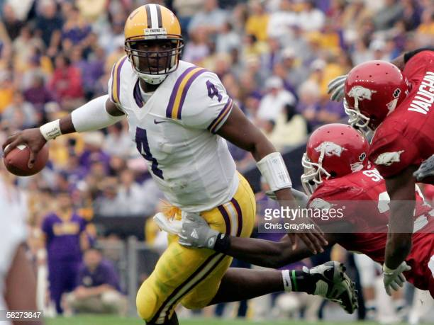 Quarterback JaMarcus Russell of the LSU Tigers avoids a tackle by Desmond Sims and Vickiel Vaughn of the Arkansas Razorbacks on November 25, 2005 at...
