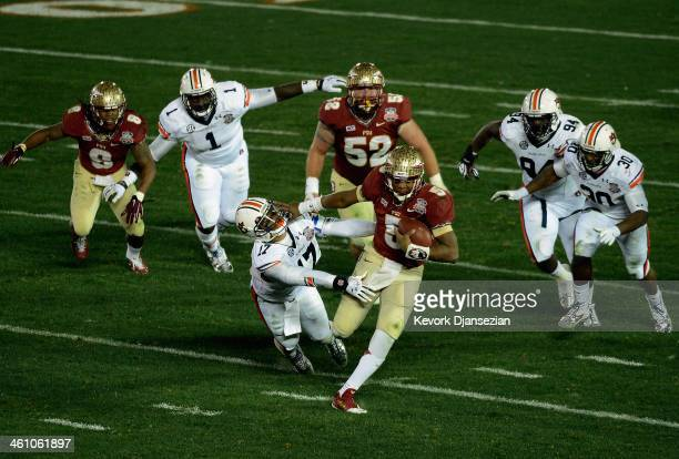 Quarterback Jameis Winston of the Florida State Seminoles runs the ball against linebacker Kris Frost of the Auburn Tigers in the second quarter...