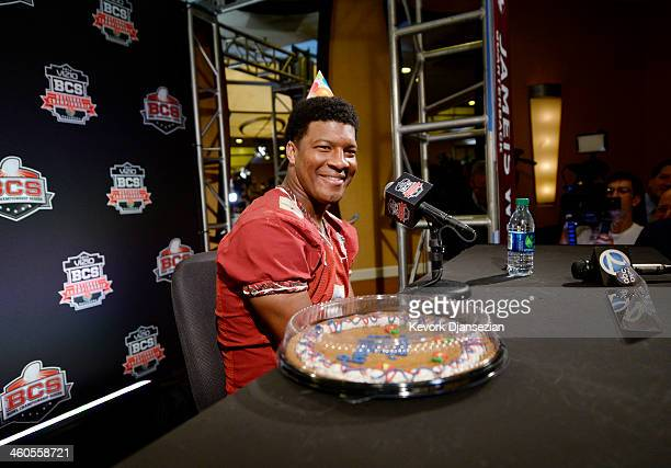 Quarterback Jameis Winston of the Florida State Seminoles wears a birthday hat as he speaks during a Vizio BCS National Championship media day news...