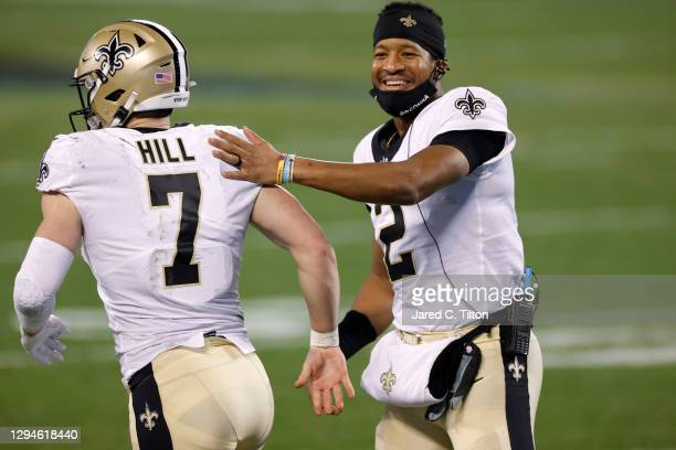 Quarterback Jameis Winston of the New Orleans Saints shares a smile as he greets teammate quarterback Taysom Hill during the second half of their...