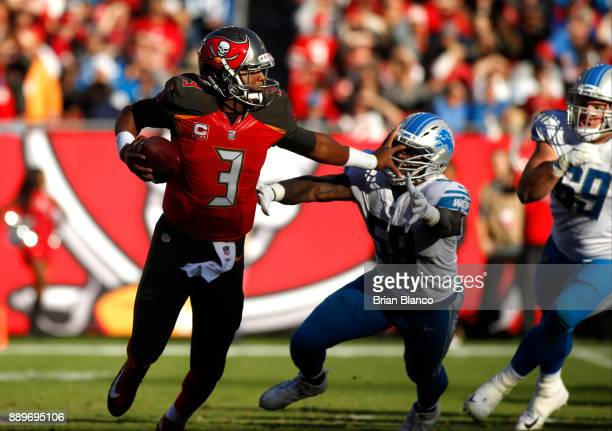 Quarterback Jameis Winston of the Tampa Bay Buccaneers fends off outside linebacker Tahir Whitehead of the Detroit Lions as he looks for a receiver...