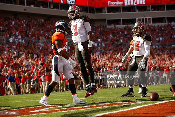 Quarterback Jameis Winston of the Tampa Bay Buccaneers leaps up in front of strong safety TJ Ward of the Denver Broncos in celebration of his...