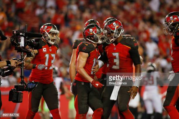 Quarterback Jameis Winston of the Tampa Bay Buccaneers runs in to celebrate in the end zone with wide receiver Adam Humphries after connecting with...