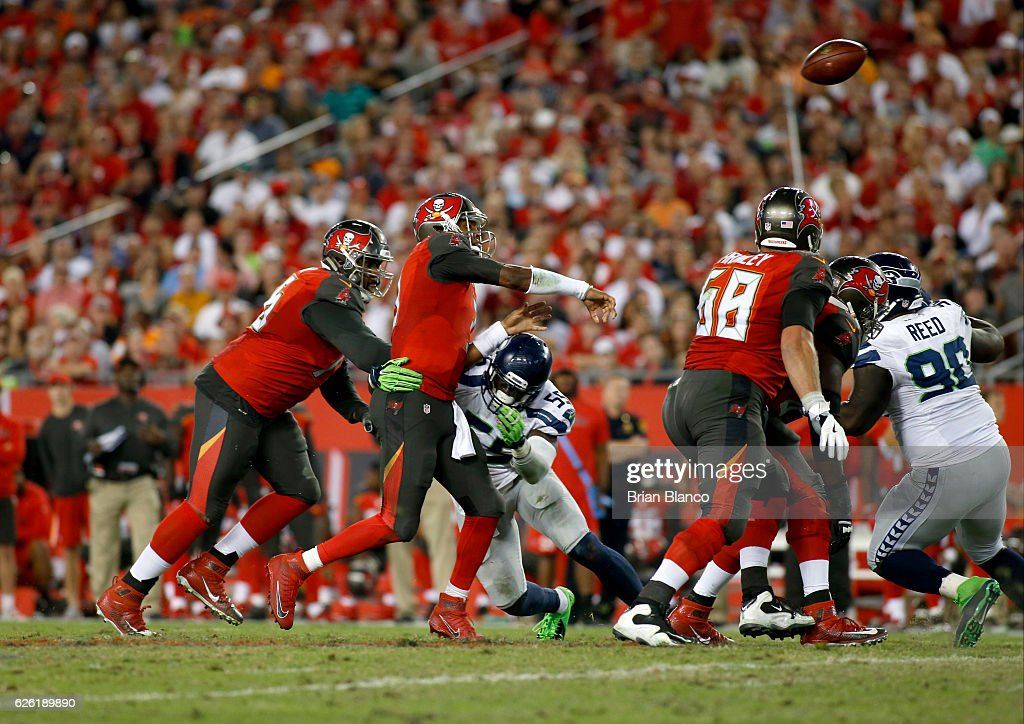 Quarterback Jameis Winston #3 of the Tampa Bay Buccaneers throws a pass while getting hit by defensive end Frank Clark #55 of the Seattle Seahawks during the third quarter of an NFL game on November 27, 2016 at Raymond James Stadium in Tampa, Florida.