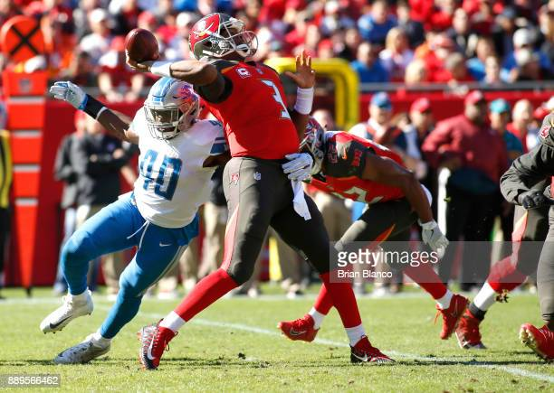 Quarterback Jameis Winston of the Tampa Bay Buccaneers throws to an open receiver while getting pressure from linebacker Jarrad Davis of the Detroit...