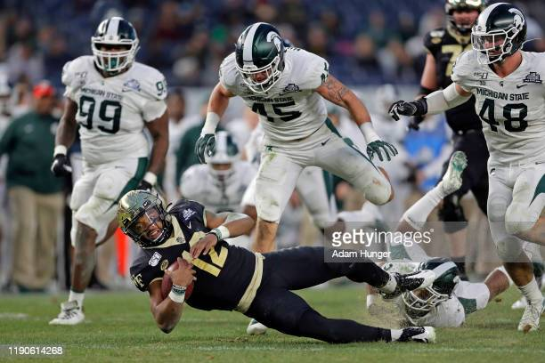 Quarterback Jamie Newman of the Wake Forest Demon Deacons is tripped up in front of linebacker Noah Harvey of the Michigan State Spartans during the...